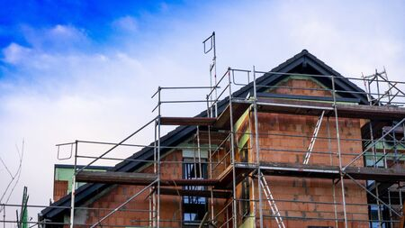 Unfinished house with scaffolding and blue sky. Symbolic for the dream of owning your own home. 写真素材