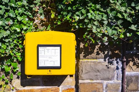 A german yellow mailbox on a wall, symbol picture.