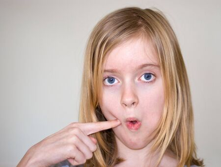 11 year old: 11 year old blond girl making face, finger in cheek