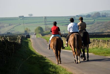 back roads: Three horse riders seen from rear on country road