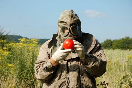 contaminated: Man in gas mask holding contaminated tomato Stock Photo