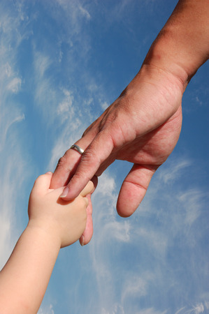 Kid holding fathers hand against blue sky