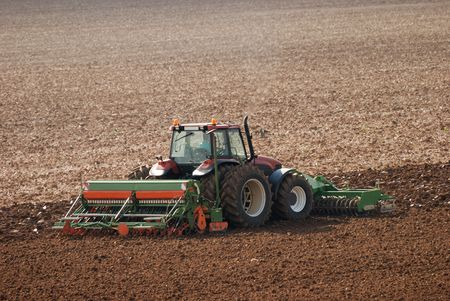 agriculture machinery: Tractor ploughing field in autumn