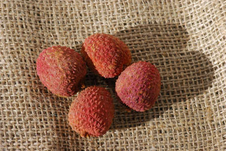 lychees: Four lychees on burlap
