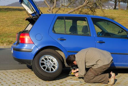 Man changing a tire on the road Stock Photo - 2612751