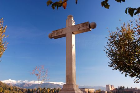 cross with snowy mountains in the background photo
