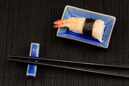 makki: Chopsticks and sushi shrimp on black bamboo mat Stock Photo