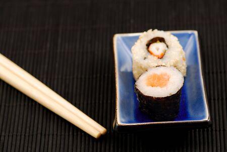 makki: Chopsticks and sushi rolls on black mat Stock Photo
