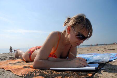 Girl lying on the beach and doing sudoku