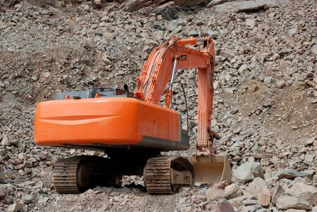gravel pit: Red excavator in a stone pit