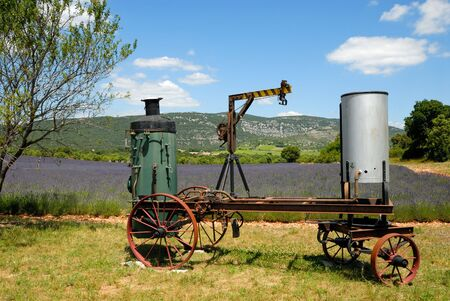distill: Old distill machine and lavender field in the Provence, France Stock Photo