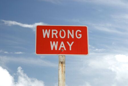 wrong way: Wrong Way sign against blue sky Stock Photo