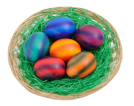 Colorful easter eggs in a nest isolated on white background photo