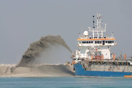 dredge: Special dredge ship pipe pushing sand to create new land in Dubai, United Arab Emirates Stock Photo