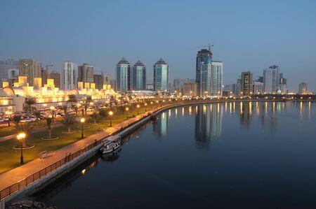 Verenigde Arabische Emiraten: Sharjah stad in de schemering. Verenigde Arabische Emiraten