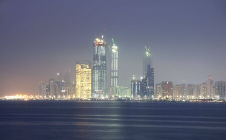 Verenigde Arabische Emiraten: Abu Dhabi Skyline in de nacht, Verenigd Konink rijk  Stockfoto