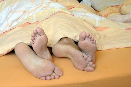 feet relaxing: Feet of a couple in bed