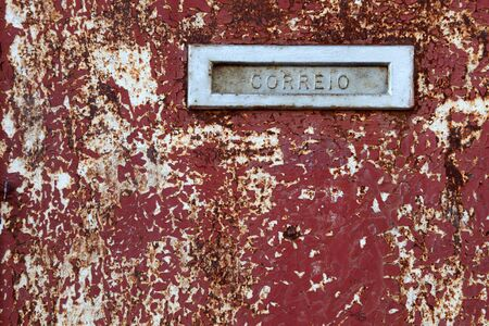 Mail box slot on the old grungy door in Portugal photo