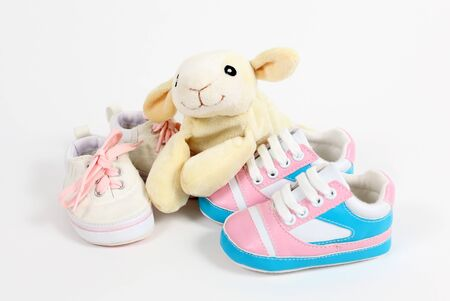 Little baby shoes and sheep over white background photo