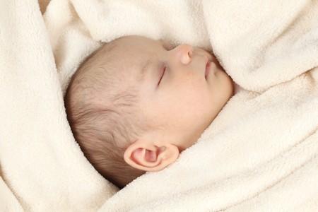 Cute baby girl sleeping in bed photo