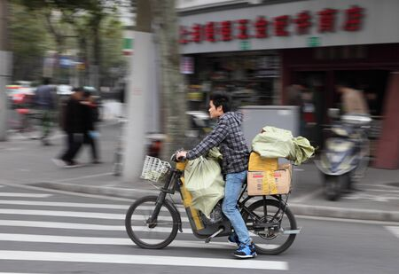 Cyclist in the street of Shanghai, China. Photo taken at 16th of November 2010 Stock Photo - 8449311