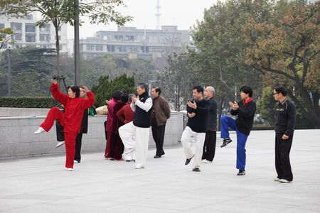 tai chi: Chinese people practicing Tai Chi Chuan in the morning at The Bund, Shanghai China. Photo taken at 17th of November 2010