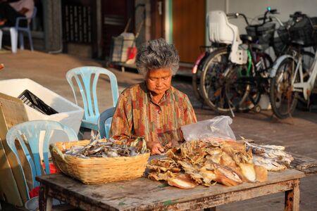 Woman selling dried fish at street market in Cheung Chau, Hong Kong. Photo taken at 3rd of December 2010 Stock Photo - 8636175