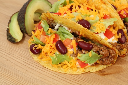 restaurant food: Mexican food - tacos filled with minced meat, cheese and beans