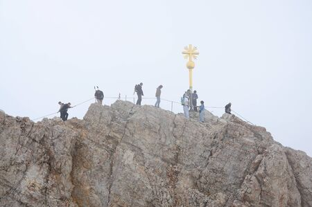 zugspitze mountain: Hikers at the cross on the summit of Zugspitze Mountain, Alps Germany. Photo taken at 5th of July 2009 Editorial