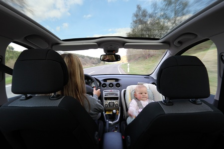 Mother driving car with her baby photo