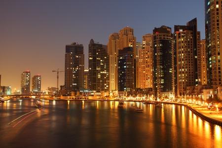 marina water: Highrise buildings at Dubai Marina illuminated at night  Stock Photo