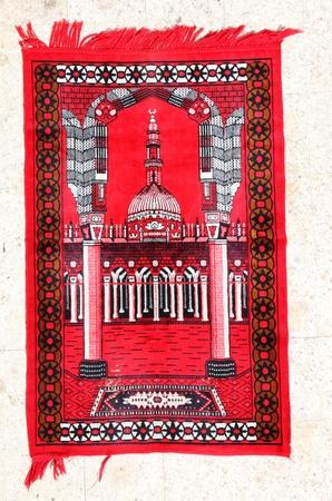 prayer rug: Red prayer carpet with a mosque