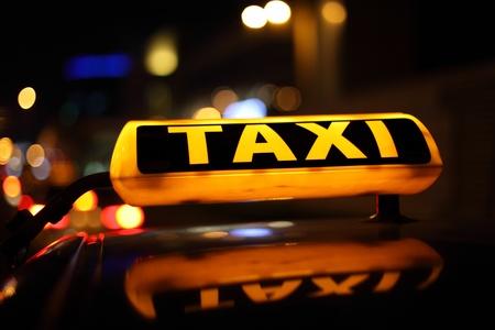 cab: Se�al de taxi amarillo en la noche Foto de archivo