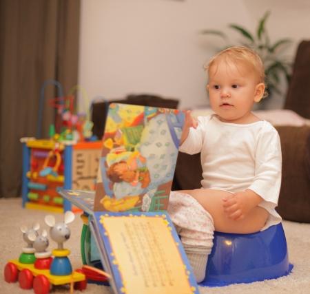 t�pfchen: Nette Kleinkind auf T�pfchen mit einem Buch