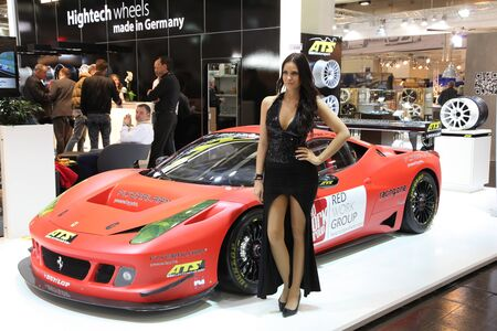 ESSEN - NOV 29: Model in front of a Ferrari shown at the Essen Motor Show in Essen, Germany, on November 29, 2011