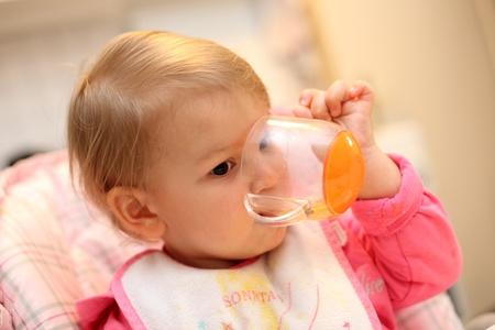babero: Ni�a de beber de una taza Foto de archivo