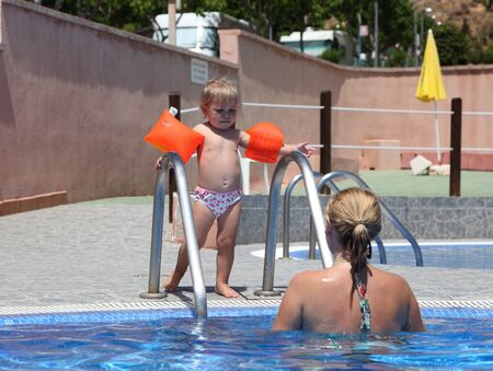 Toddler girl at the swimming pool with her mommy photo