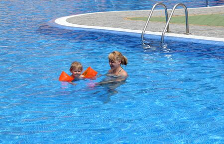 Girl with her mother in the swimming pool photo