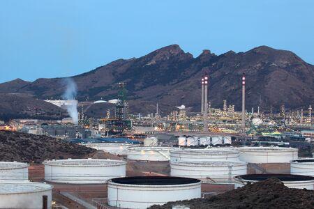 benzin: Oil refinery facilities illuminated at dusk