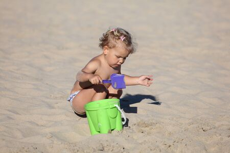 Toddler girl playing on the beach photo