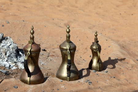 Traditional Bedouin coffee pots at fireplace in the desert photo