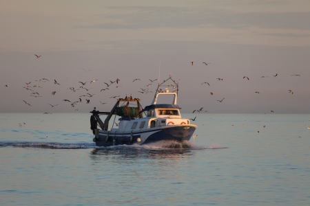 Fishing boat on its way back to the home harbor photo