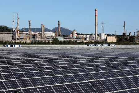 petrochemistry: Solar power station with a oil refinery in the background