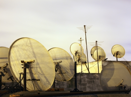 Satellite dishes on the rooftop at night photo