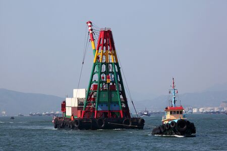 tugboat: Tugboat with a crane barge in the harbour of Hong Kong Stock Photo