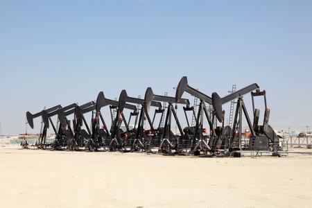opec: Black oil pump jacks in the desert of Bahrain Stock Photo