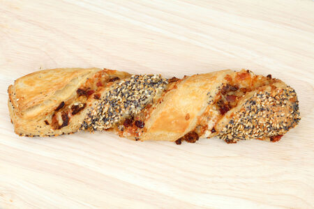 Traditional german cheese pretzel stick with sesame and poppy seeds photo