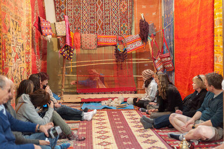 artisanry: Tourists watching moroccan woman weaving traditional carpet. Morocco, Africa