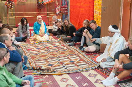 artisanry: Moroccan rug sellers showing traditional berber carpets to tourists. Morocco, Africa Editorial