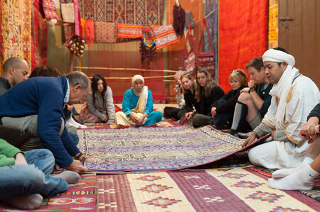 berber: Moroccan rug sellers showing traditional berber carpets to tourists. Morocco, Africa Editorial